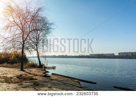 Beach Near A Wide River On A Sunny Autumn Day. Multi-storey Buildings Across The River. Cityscape An