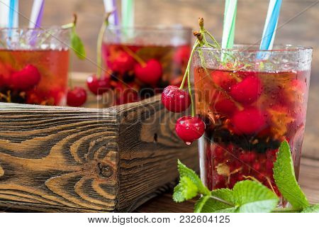 Glasses Of Refreshing Drink Flavored With Fresh Fruit And Decorated With Cherries Covered With Dew D