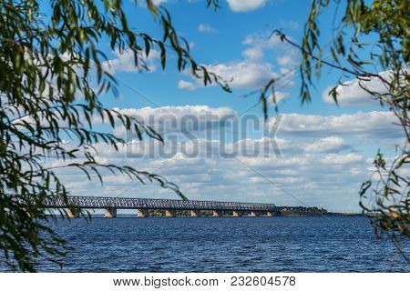 Colorful Summer Landscape On River With Beautiful Clouds In The Sky  And Bridge Out Focus, Green Lea