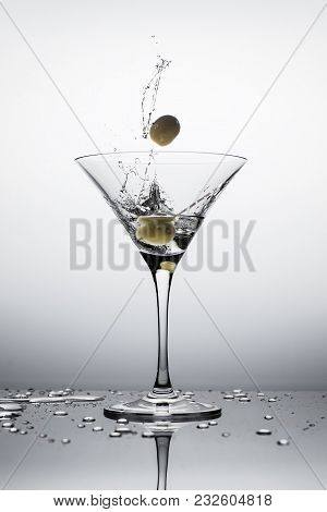 Falling Olives Making A Splash Of Vodka In Martini Glass. White Background.