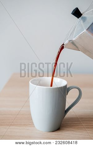 Pouring A Cup Of Hot Coffee Into The Glass For Breakfast.