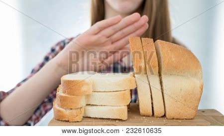 Gluten Intolerance Concept. Young Girl Refuses To Eat White Bread - Shallow Depth Of Field - Selecti