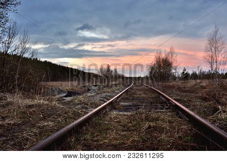 The Outgoing Railway Rails On The Background Of The Red Sunset