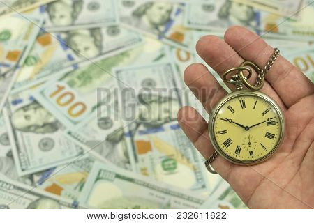 Pocket Watch With A Chain In Hand On American One Hundred Dollar Bills Laid Out On The Table As A Bl