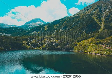 Beautiful Mountains Lake With A Reflection Of The High Green Mountains Peaks, On The Blue Sky Backgr