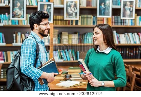 Couple Of Smart Students With Books Talking In The Library Before Bookshelves