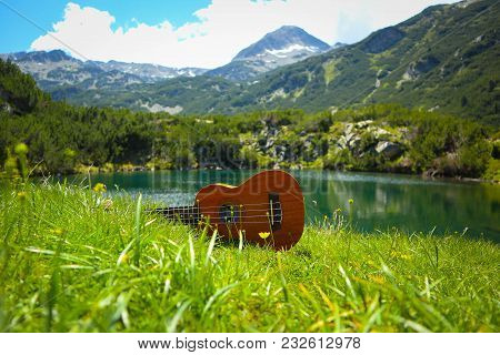 Romantic View Of The Ukulele Guitar At The Mountain Nature Green Meadow. Photo Depicts Musical Instr