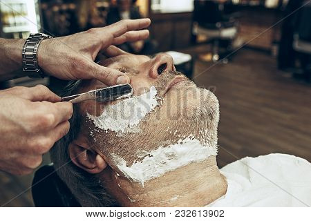 Close-up Side Top View Handsome Senior Bearded Caucasian Man Getting Beard Grooming In Modern Barber