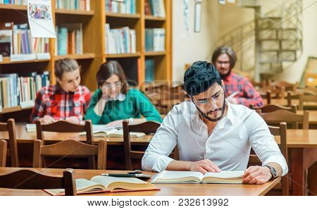 Bearded Student Man Wears White Shirt Studying With Books In The Library