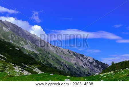 Beautiful View On The High Green Mountains Peaks, On The Blue Sky Background. Mountain Hiking Paradi