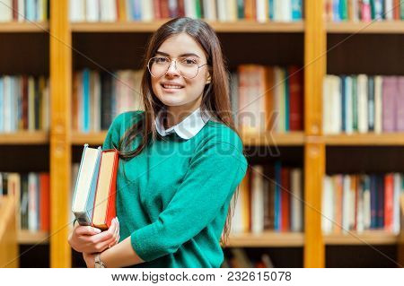 Portrait Of Young Beautiful Student Girl Wears Glasses And Green Sweater Holding Books Before Booksh