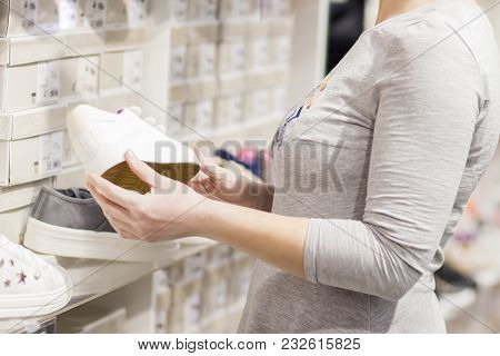Close-up Of Girl In Shoe Shop Chooses Sneakers. Shopping In Boutique Of Fashionable Shoes. A Young G