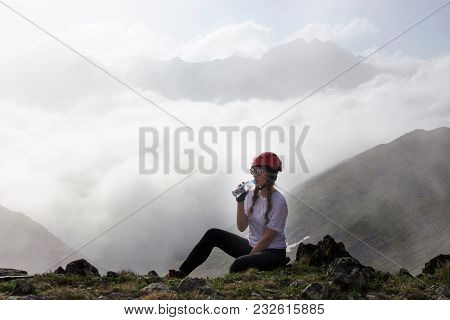 Girl Hiker Drinking Water On The Mountain.