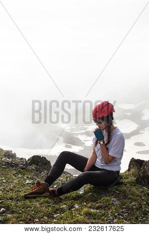 Girl In A Hike Sits On Top Of A Mountain.