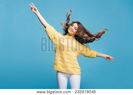 Attractive Young Lady Posing On Blue Background. Pretty Girl Dance And Having Fun. Hair Flying