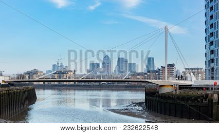 Modern Foot Bridge Across River With London's Financial District In Background