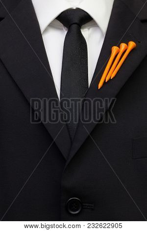 The Detail Of Wedding Suit With Golf Design. Orange Golf Tees On The Flap Of Black Jacket.