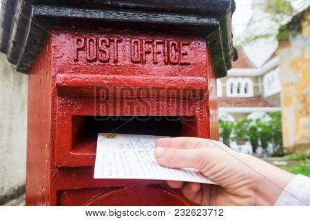 Closeup On A Male Hand Putting A Letter In A Red Letterbox. Concept Of Vintage Type Of Communication