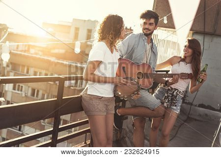 Three Young Friends Having Fun At Rooftop Party, Playing Guitar And Singing. Focus On The Man Playin