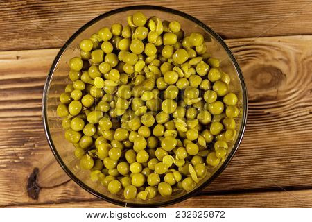 Canned Green Peas In Glass Bowl On Wooden Table