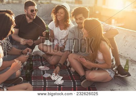 Group Of Young People Sitting On A Picnic Blanket, Having Fun While Playing Cards On The Building Ro