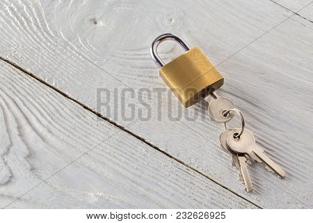 Locked Padlock With Silvered Keys On White Wooden Background. Estate And Security Concept With Symbo