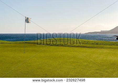Green Golf With Flag And Hole Facing Atlantico Ocean In Santa Cruz De Tenerife