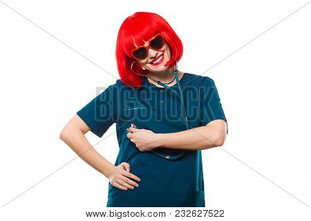 Beautiful Happy Cheerful Woman Doctor Looking In Camera Funny Showing Sign With Red Wig And Sunglass