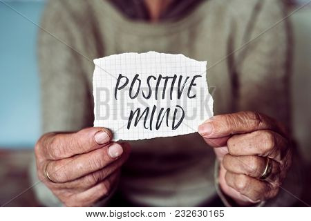 closeup of an old caucasian woman showing a note with the text positive mind written in it