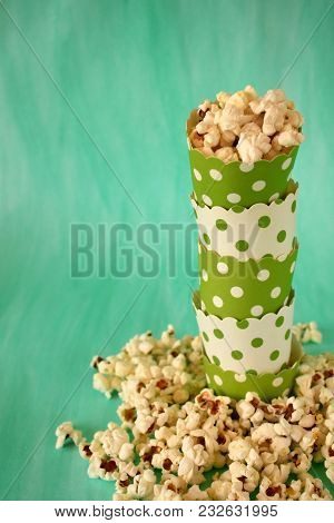 Popcorn In Stack Of Paper Cups On Green Background