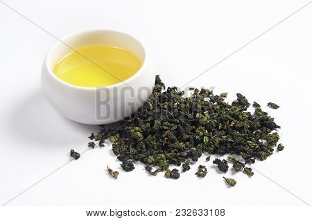 Dry Green Chinese Tea And Beverage In Cup On A White Background Close-up. Tie Guan Yin