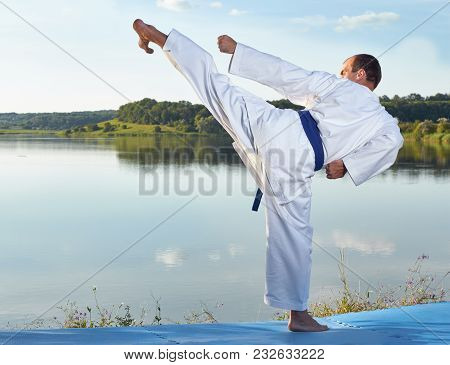 Kicking Is Beating Athlete On A Blue Mats