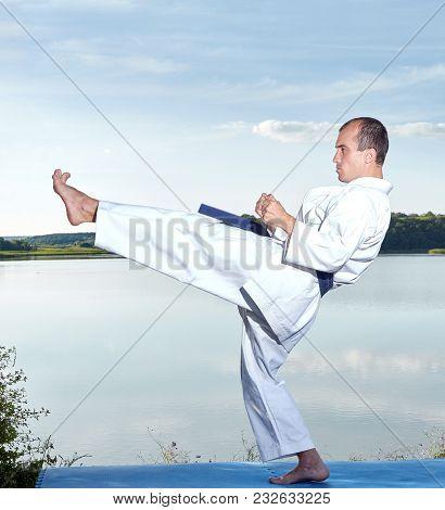 On Coast Of Lake Athlete Beats A Kick Leg Forward