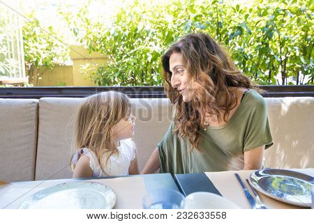 Woman Telling A Happy Story To Little Girl In Restaurant