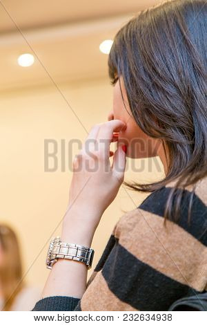 A Thoughtful Brunette Girl With A Clock On Her Arm