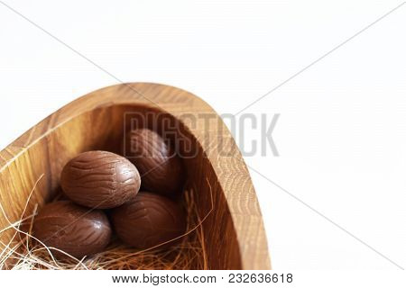 Five Brown Chocolate Easter Eggs  In Wooden Plate On White Background As Template For Greeting Card