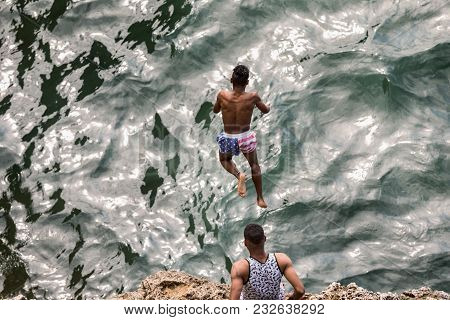 The Boys From Havana Are Jumping From The Rocks Into The Sea. Cuba, Havana. Jump, Danger. Young Cuba