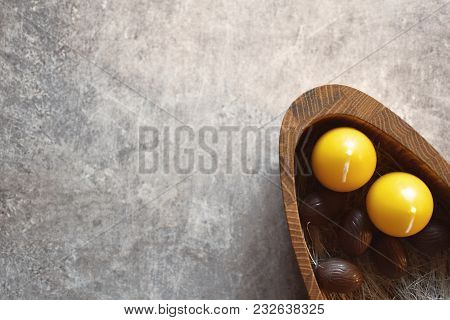 Top View Of Five Brown Chocolate Easter Eggs And Two Yellow Candles In Wooden Plate On Grunge Grey B