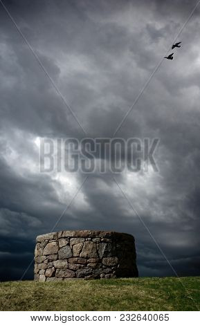 An Old Stone Well In The Middle Of A Field With Storm Clouds In The Background.