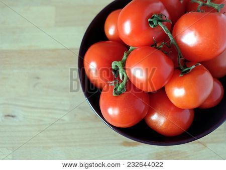 Still Life With Red Ripe Tomatoes In Part Of Violet Bowl On Wooden Background Top View Closeup