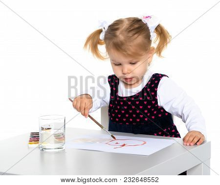 A Little Girl Draws At A Table On A Piece Of Paper. The Concept Of A Happy Childhood, Creativity, Le
