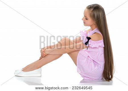 A Teenage Girl In A Short Dress Sits On The Floor And Holds Her Knees With Her Hands. The Concept Of