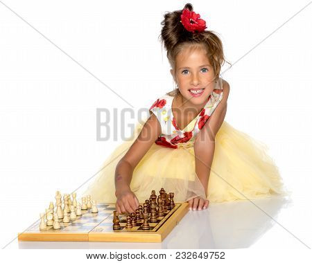 A Little Girl Is Playing Chess. The Concept Of Creative Education Of A Child, Training Of Thinking.