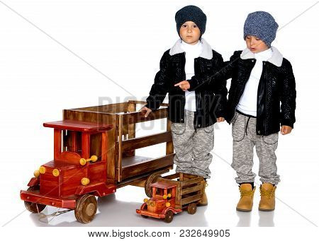 Two Little Boys Play With Wooden Cars. In Autumn Jackets And Hats. Isolated On White Background.