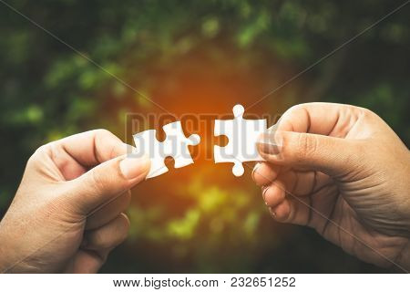 Two Hands Trying To Connect Couple Puzzle Piece With Forest Background; One Part Of Whole; Symbol Of