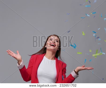 Beautiful happy woman at celebration party with confetti .Birthday or New Year eve celebrating concept