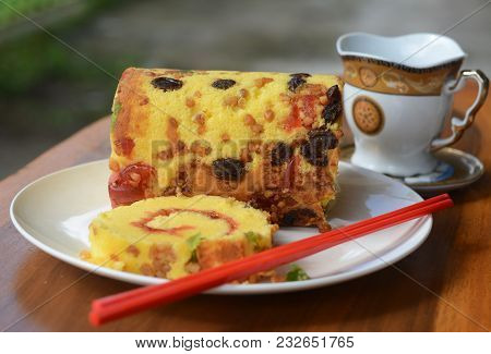 Delicious Homemade Roll Cake Reserved On A White Porcelain Plate On Brown Wooden Table. Indonesian F