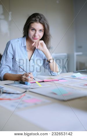 Young woman sitting in office table, looking at laptop computer screen