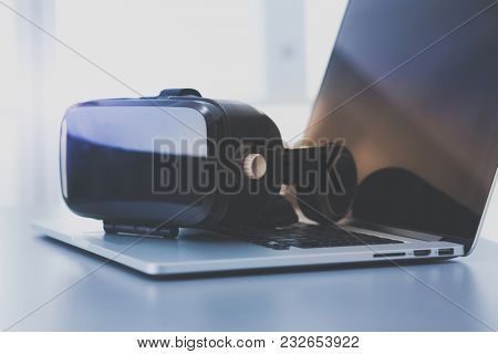 Virtual reality goggles on desk with laptop