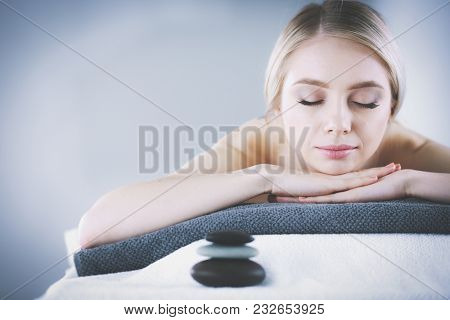 Young woman lying on a massage table,relaxing . Woman. Spa salon